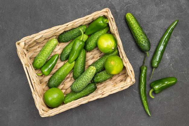 Gurken, paprika und limetten im rattankorb. grüne paprika auf dem tisch. schwarzer hintergrund. flach legen