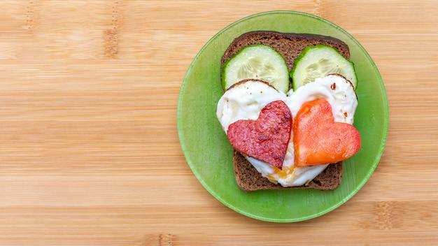 Gurkensandwich, herzförmige rühreier mit würstchen und herzförmiger tomate auf einem grünen teller