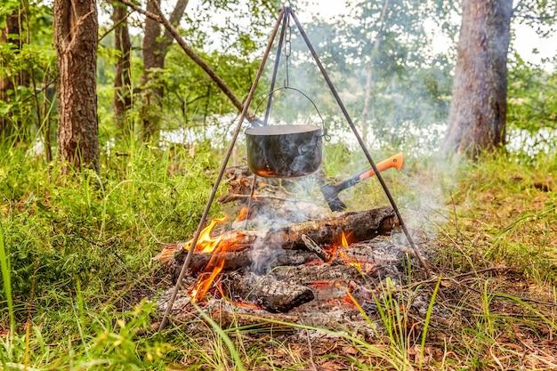 Gusseisentopf kocht über offenem feuer in einem campingplatz im wald an sonnigem sommertag