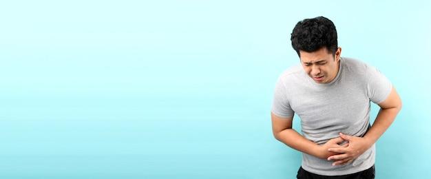 Gut aussehend von asiatischen mann sick hat bauchschmerzen an der blauen wand isoliert.