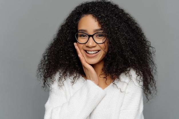 Gut aussehende afro-frau berührt die wange, lächelt glücklich, genießt komplimente