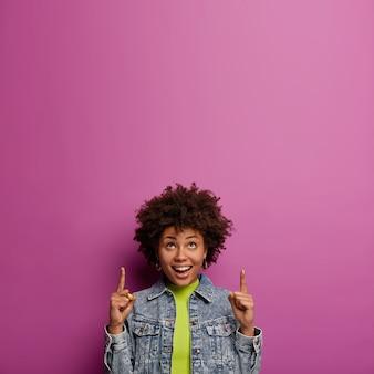 Gut aussehende afroamerikanische frau zeigt oben mit beiden zeigefingern