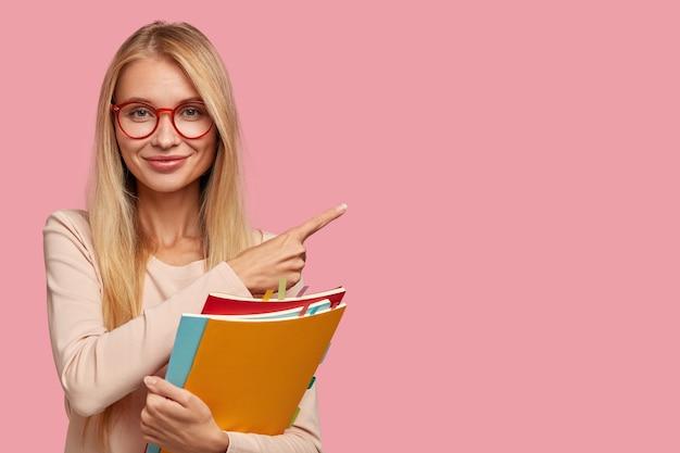 Gut aussehende blonde studentin posiert gegen die rosa wand