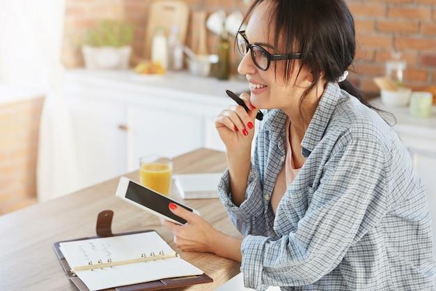 Gut aussehende brünette frau, die zu hause ist, verwendet moderne tablette, um kontakte mit freunden oder verwandten herzustellen