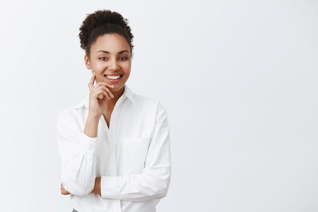 Gut aussehende erfolgreiche dunkelhäutige unternehmerin, die mit höflichen und freundlichen lächeln-angestellten zuhört, sich für einen neuen job bewirbt, person interviewt, finger auf wange hält und breit lächelt