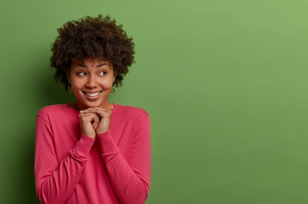 Gut aussehende erfreute ethnische lockige frau hat gute laune und drückt positive gefühle aus, hält hände unter kinn, schaut zur seite, hat ein zahniges lächeln, gekleidet in rosigen pullover, isoliert auf grüner wand