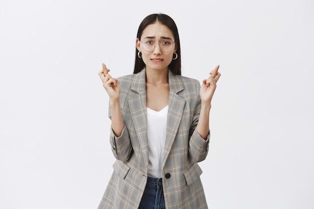 Gut aussehende erwachsene unternehmerin in brille und jacke, daumen drücken und stirnrunzeln, während auf den traum gehofft wird