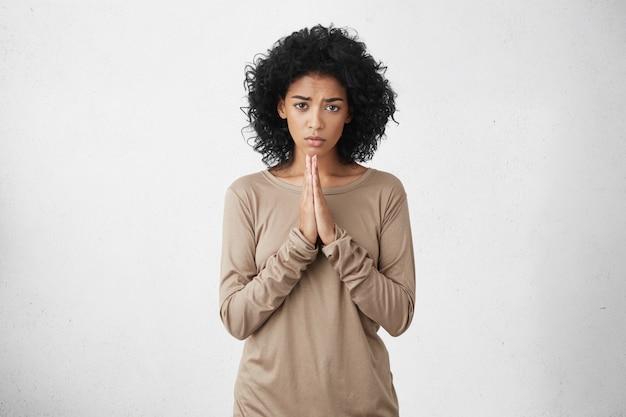 Gut aussehende frau, die lässig gekleidet ist und die handflächen vor sich zusammengedrückt hält, bedauernd und traurig aussieht und um vergebung bittet. menschliche mimik, emotionen und körpersprache