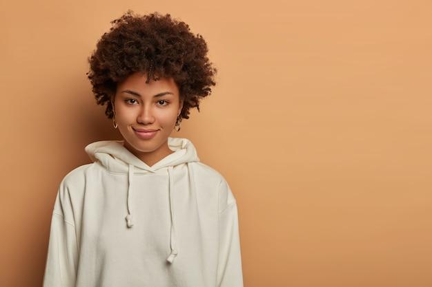 Gut aussehende frau hat afro-haare, hat direkten blick und zartes lächeln
