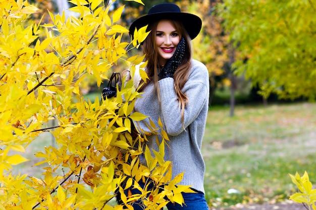 Gut aussehende frau mit langen haaren trägt jeans und handschuhe, die in sicherer haltung auf naturhintergrund stehen. foto im freien des hübschen weiblichen modells im trendigen grauen pullover, der im park am herbsttag geht.