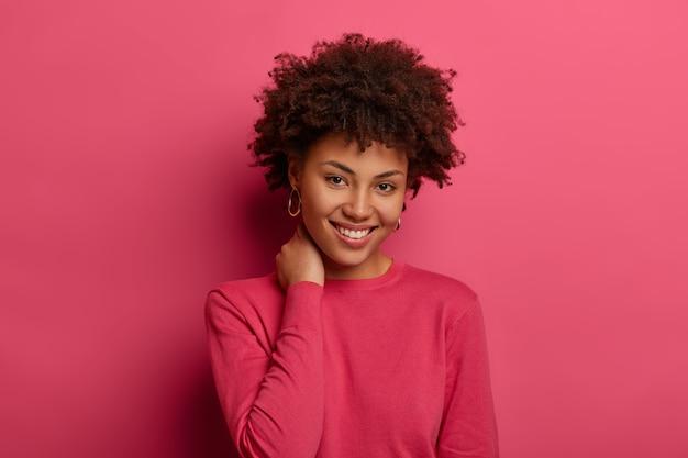 Gut aussehende frau mit lockigem haar, hält die hand am hals, lächelt sanft, trägt einen purpurroten freizeitpullover und schaut fröhlich in die kamera