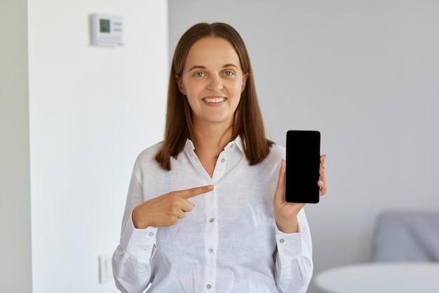 Gut aussehende frau mit weißem hemd, die ein smartphone in den händen hält und mit dem zeigefinger auf den leeren bildschirm zeigt und mit einem charmanten lächeln in die kamera schaut.