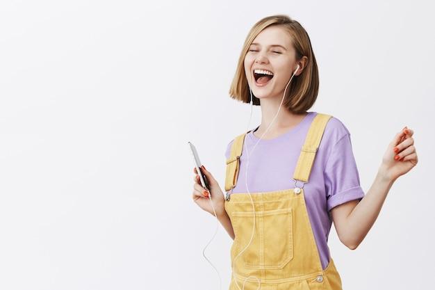 Gut aussehende freudige frau, die mit geschlossenen augen sorglos tanzt, smartphone hält und musik in kopfhörern hört