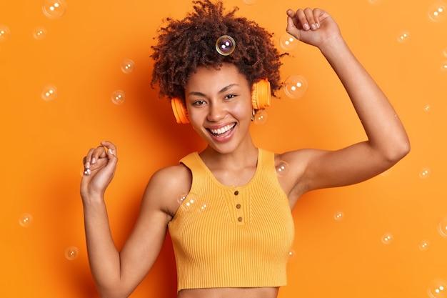 Gut aussehende fröhliche frau tanzt sorglos hält die arme hoch, trägt stereokopfhörer an den ohren, bewegt sich mit rhythmus der musik und lächelt breit isoliert über die leuchtend orangefarbene wand