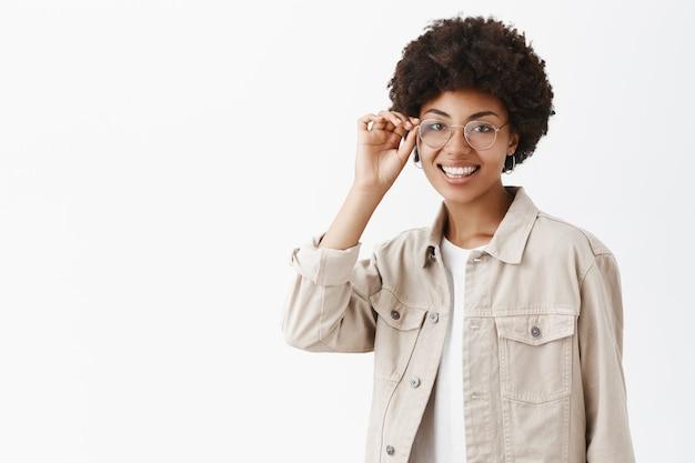 Gut aussehende fröhliche und weibliche afroamerikanerin mit afro-frisur, berührendem brillenrand und lächelnd, selbstbewusst kann sie alles