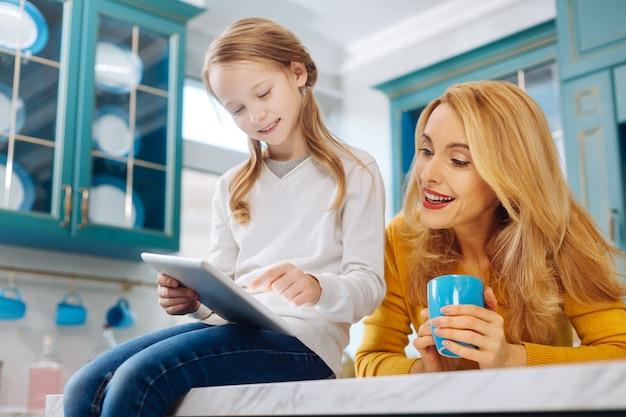 Gut aussehende, glückliche, blonde, schlanke mutter, die lächelt und eine tasse tee hält, während ihre tochter eine tablette benutzt, während sie auf dem tisch sitzt