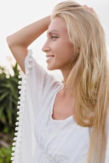 Gut aussehende glückliche frau gekleidet in der weißen bluse, die weg schaut