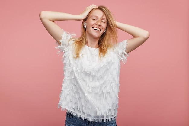 Gut aussehende glückliche junge reizende dame mit foxy haar, die ihren kopf mit erhobenen händen hält und breit lächelt, während musik mit geschlossenen augen hört, lokalisiert über rosa hintergrund