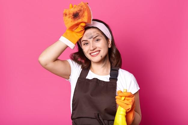 Gut aussehende hausfrau posiert mit der hand, die den kopf berührt, waschmittel hält, aufrichtig lächelt und einen angenehmen gesichtsausdruck hat