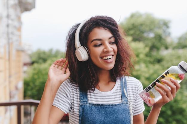 Gut aussehende junge afrikanische frau ohne make-up, die spaß mit lieblingsmusik im freien hat