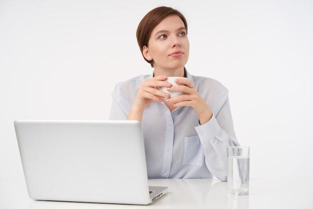Gut aussehende junge braunhaarige frau mit natürlichem make-up, die eine tasse tee in erhobenen händen hält, während sie mit ihrer arbeit pause macht und auf weiß sitzt