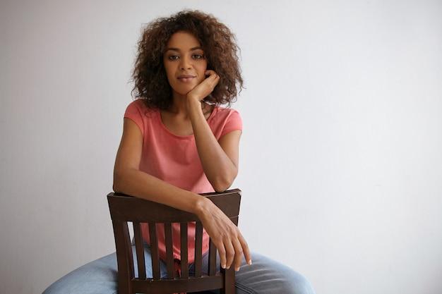 Gut aussehende junge dunkelhaarige lockige frau, die in freizeitkleidung posiert, mit der hand auf dem rückenstuhl sitzt und sich anmeldet