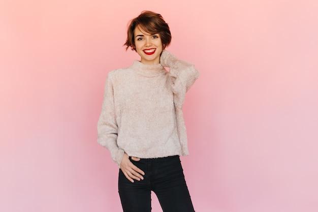 Gut aussehende junge frau im pullover, die vorne schaut