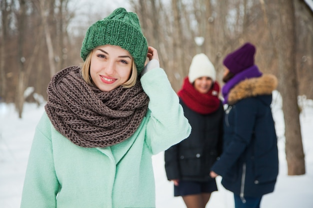 Gut aussehende junge frau in grüner strickmütze und snood, die draußen aufwirft.