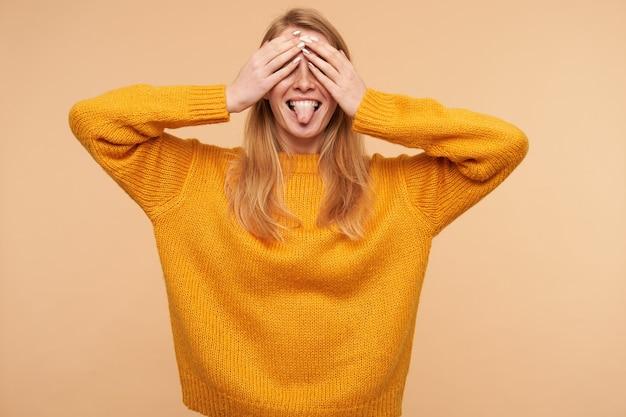 Gut aussehende junge freudige langhaarige rothaarige dame, die ihre zunge herausstreckt und augen mit erhobenen handflächen kegelt, während sie spaß hat, isoliert auf beige