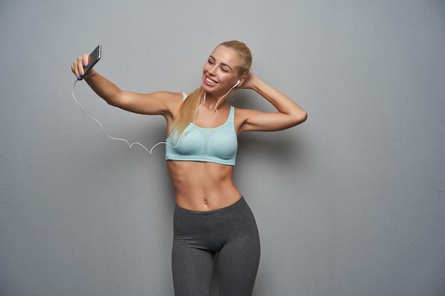 Gut aussehende junge fröhliche schlanke frau mit langen blonden haaren, die foto von sich selbst mit smartphone macht, während sie über grauem hintergrund aufwirft, minze sportliches oberteil und graue leggins tragend