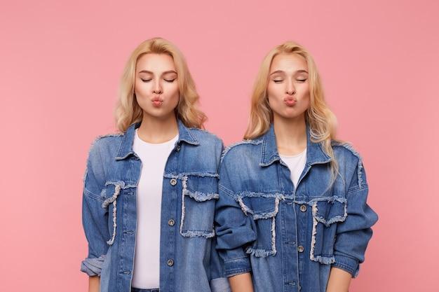 Gut aussehende junge positive blonde damen in jeansmänteln und weißen t-shirts halten ihre augen geschlossen, während sie ihre lippen in luftkuss falten, isoliert über rosa hintergrund