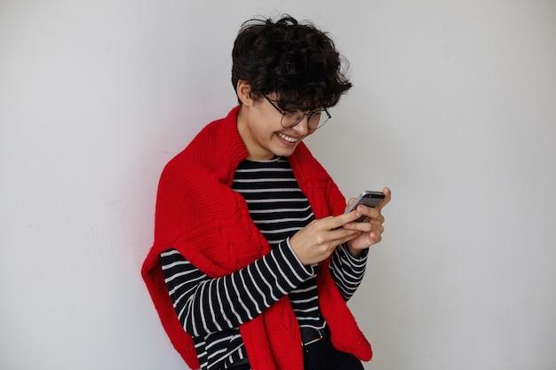 Gut aussehende junge positive lockige brünette frau mit kurzem haarschnitt, der gestreiften pullover und roten wollpullover trägt, während über weißem hintergrund mit handy steht