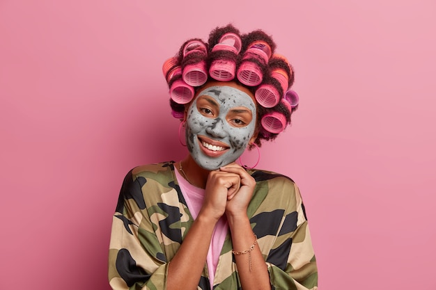 Gut aussehende lächelnde hausfrau unterzieht sich schönheitsbehandlungen mit gesichtsmaske