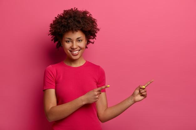 Gut aussehende lockige frau zeigt beiseite, empfiehlt schönes produkt, zeigt platz für werbung, lächelt breit, sagt probieren sie es aus, isoliert über rosa wand. kopieren sie platz für ihre werbung