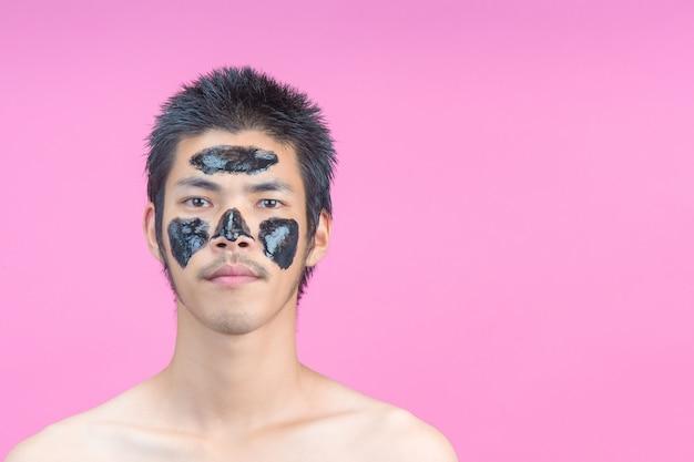 Gut aussehende männer, die schwarze kosmetik auf ihre gesichter auftragen und ein rosa haben.