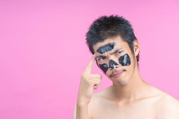 Gut aussehende männer, die schwarze kosmetik auf ihre gesichter auftragen und verschiedene haltungen mit einem rosa zeigen.