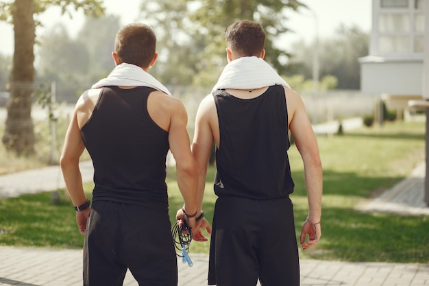 Gut aussehende männer in sportkleidung, die in einem park steht