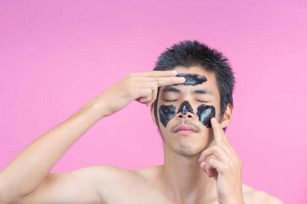 Gut aussehende männer verwenden ihre hände, um schwarze creme auf ihre gesichter aufzutragen und haben ein rosa.