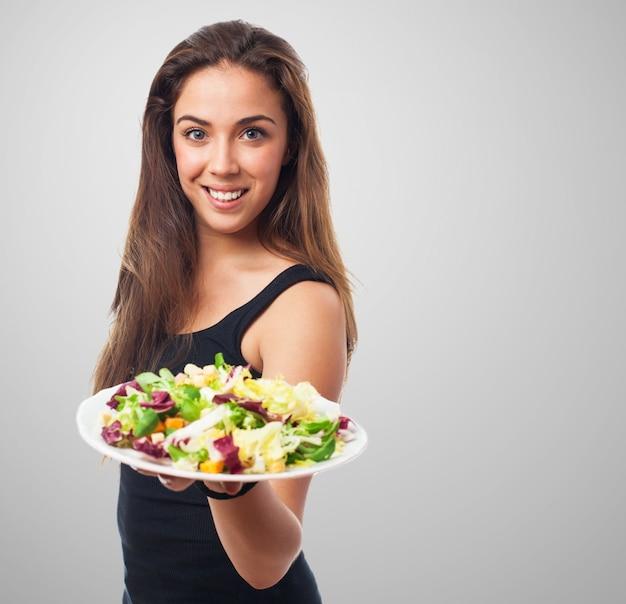 Gut aussehende modell einen teller mit salat hält