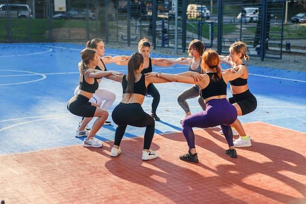Gut aussehende schlanke leichtathletikfrauen, die hockende übungen machen, die im kreis auf dem freiluftstadion im modernen stadtpark stehen.