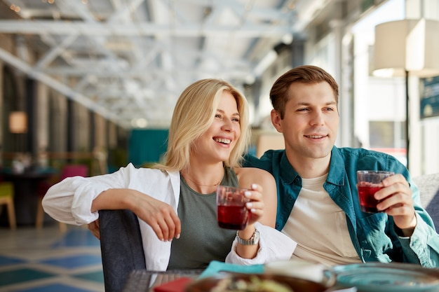 Gut aussehende schöne paare sitzen und unterhalten sich mit freunden vor ihnen im restaurant
