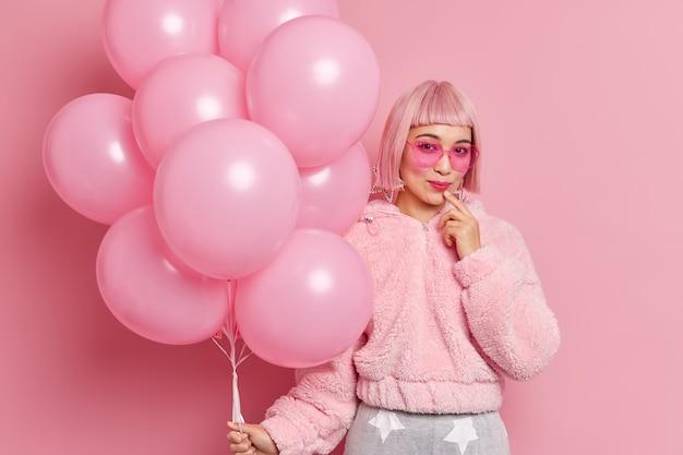 Gut aussehende stilvolle asiatische frau trägt rosa perücke mit fransen trendige sonnenbrille pelzmantel hält bündel von heliumballons bereit für hühner party posen drinnen