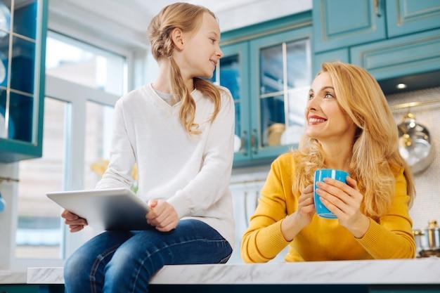 Gut aussehende üppige blondhaarige schlanke mutter, die lächelt und eine tasse tee hält, und ihre tochter, die eine tablette benutzt, während sie auf dem tisch sitzt