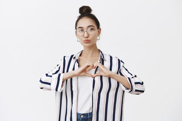 Gut aussehende weibliche modebloggerin, die herz mit händen über brust formt, lippen in kuss faltet, mwah gibt, foto für fangemeinde macht, über graue wand mit niedlicher brötchenfrisur in gläsern stehend