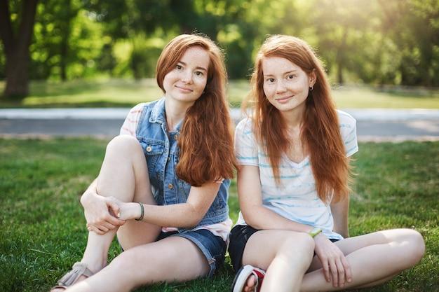 Gut aussehende zwei frauen mit roten haaren und sommersprossen, die auf gras nahe dem universitätscampus sitzen und chillen