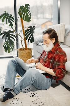 Gut aussehender älterer mann. arbeiten mit laptop. auf dem boden sitzen. fastfood essen.