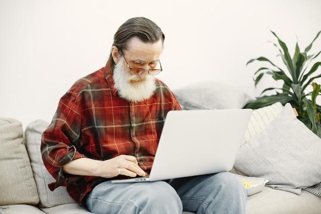Gut aussehender älterer mann. arbeiten mit laptop. auf der couch sitzen.