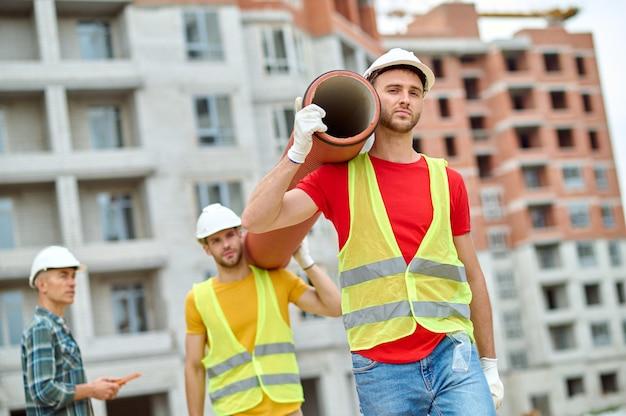 Gut aussehender arbeiter in einem bauarbeiterhelm und baumwollhandschuhen und sein kollege, der ein schweres abflussrohr trägt, das von einem ingenieur überwacht wird