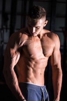 Gut aussehender athletischer junger mann im fitnessstudio