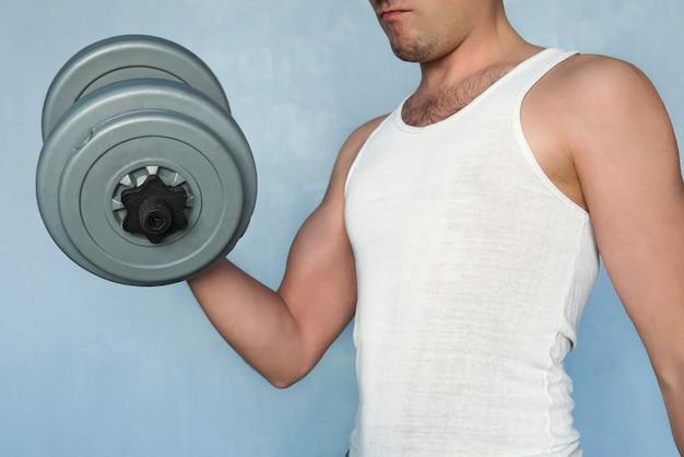 Gut aussehender athletischer mann im training, der muskeln mit hantel aufpumpt. einfach kein sportlicher, nicht muskulöser typ schüttelt ihre großen bizeps-hanteln. heimübung. sportlicher lebensstil. durchschnittliche person